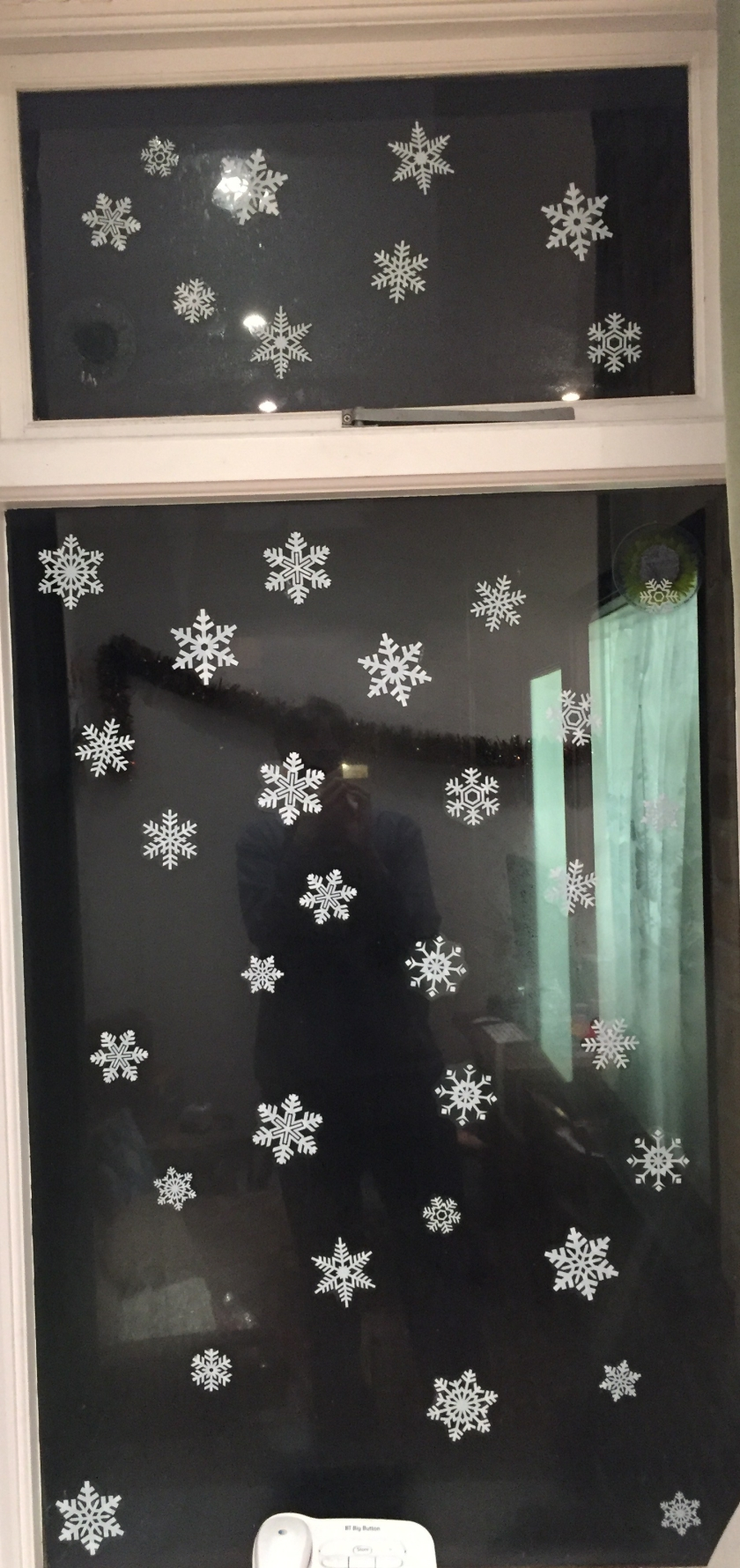 Varied white snowflake patterns stuck all over the lounge window