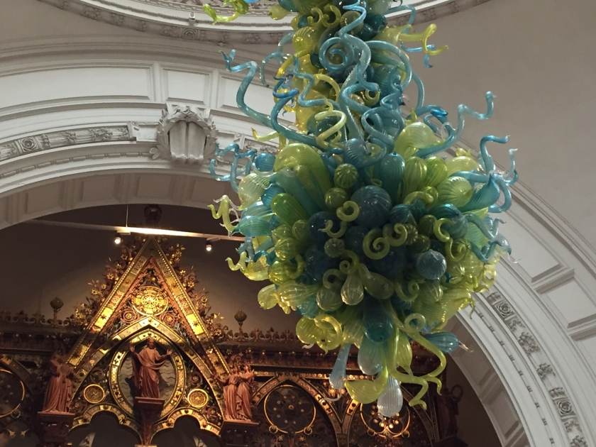 Chandelier in the main hall of the V&A Museum. It has many curved intertwining tubes with bulbous ends, in a mixture of blue and green colours, forming a teardrop-like shape overall.