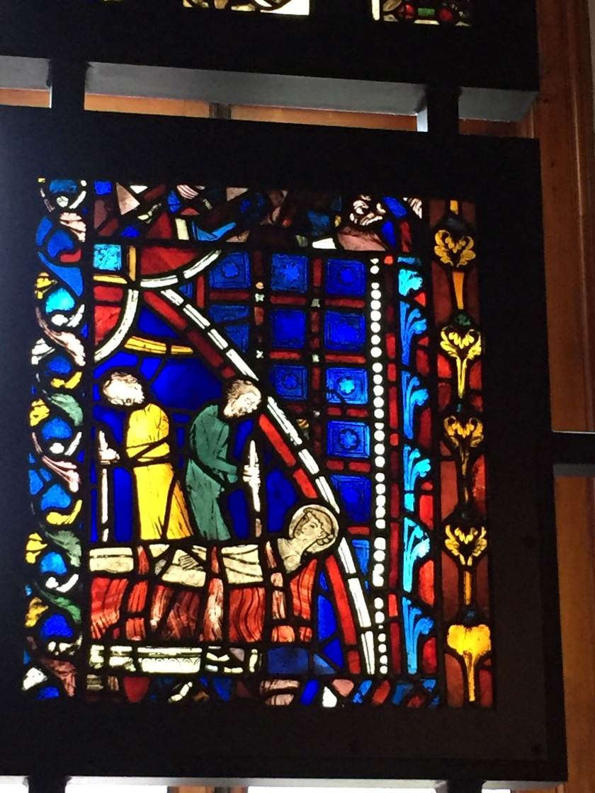 Stained glass window with a predominantly blue background, depicting a man laid on a bench, tied down by 3 straps, while 2 men back to back next to him holding stick-shaped objects.