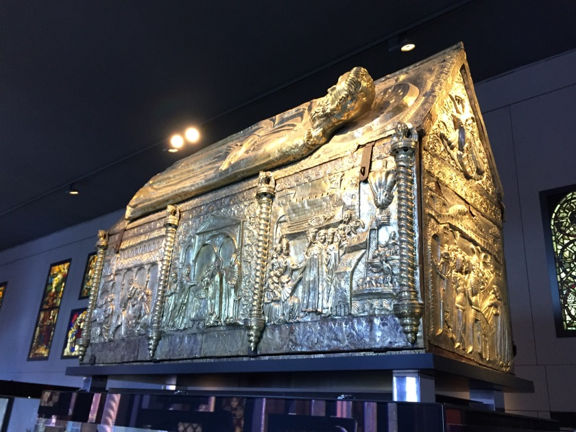A massive and very ornate gold structure in the shape of long building rectangular building with a sloping roof. It's covered in embossed scenes depicting a variety of people and objects.