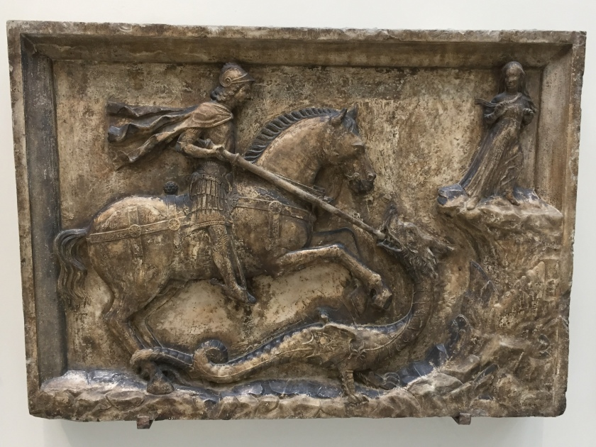 An embossed bronze depiction of St George riding a horse to rescue a woman trapped on a ledge, thrusting his lance into the mouth of the dragon that's trying to attack her.