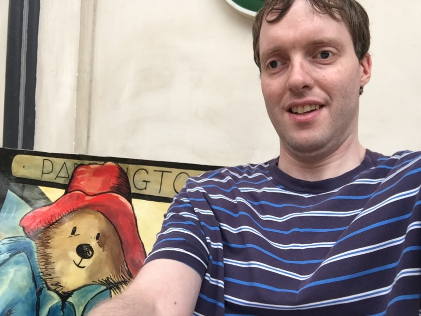 Selfie of me sitting on a bench that's decorated with a painting of Paddington Bear, so it looks like he's sitting next to me and joining in the selfie with a smile.