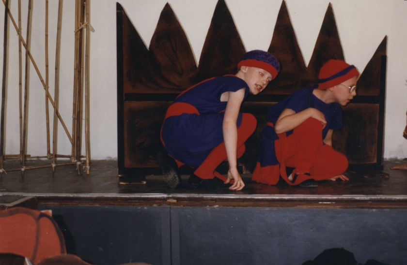 Me and another boy, dressed in blue tops and red trousers, with blue and red hats, crouching on stage next to a spiky wall, hiding from the people we're spying on.