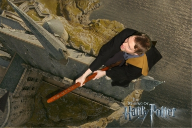 Overhead view of Glen in a brown robe with yellow inner lining, flying on a broomstick over Hogwarts Castle.