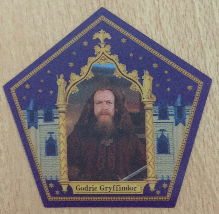 5-sided card with a blue background and gold detailing, featuring the bearded Godric Gryffindor in an ornate gold frame in the centre, part of his sword just visible at the bottom of the frame.