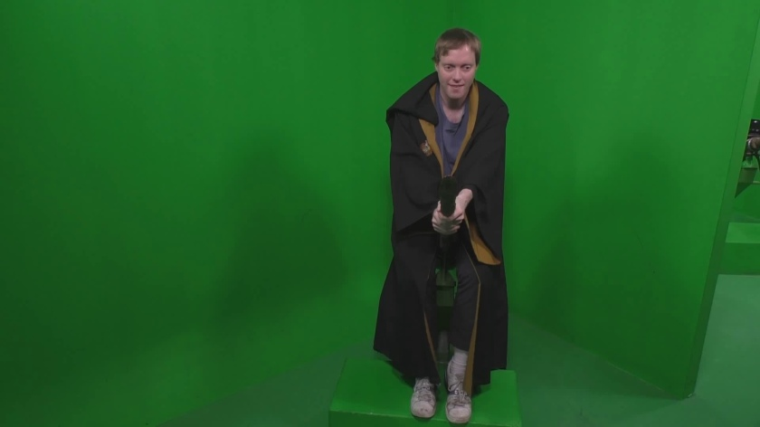 In front of a plain green background, Glen is wearing a brown robe with a yellow inner lining visible, while mounted on a broomstick as if ready to fly, with his hands clasped around the handle at the front.