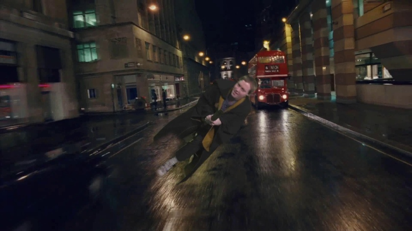 Glen in a brown robe flying on a broomstick, down the middle of a busy London road at night, with a red London bus in the background.