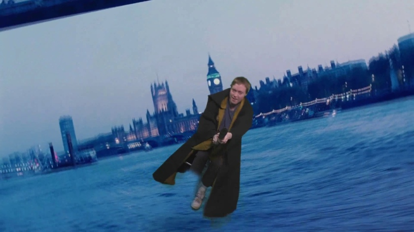 Glen in a brown robe, flying on a broomstick over the River Thames, with Westminster Bridge, Big Ben and the Houses Of Parliament in the background.