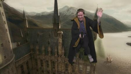 Glen in a brown robe, smiling and waving as he hovers on a broomstick over Hogwarts Castle.