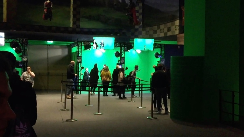 Queuing area in front of booths that have completely green walls and flooring.