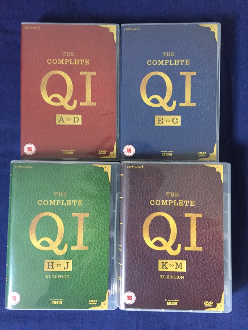 Collection of 4 DVD boxsets for The Complete QI, for A to D (red), E to G (blue), H to J (green) and K to M (brown). all the cases are designed to look like old fashioned book covers.