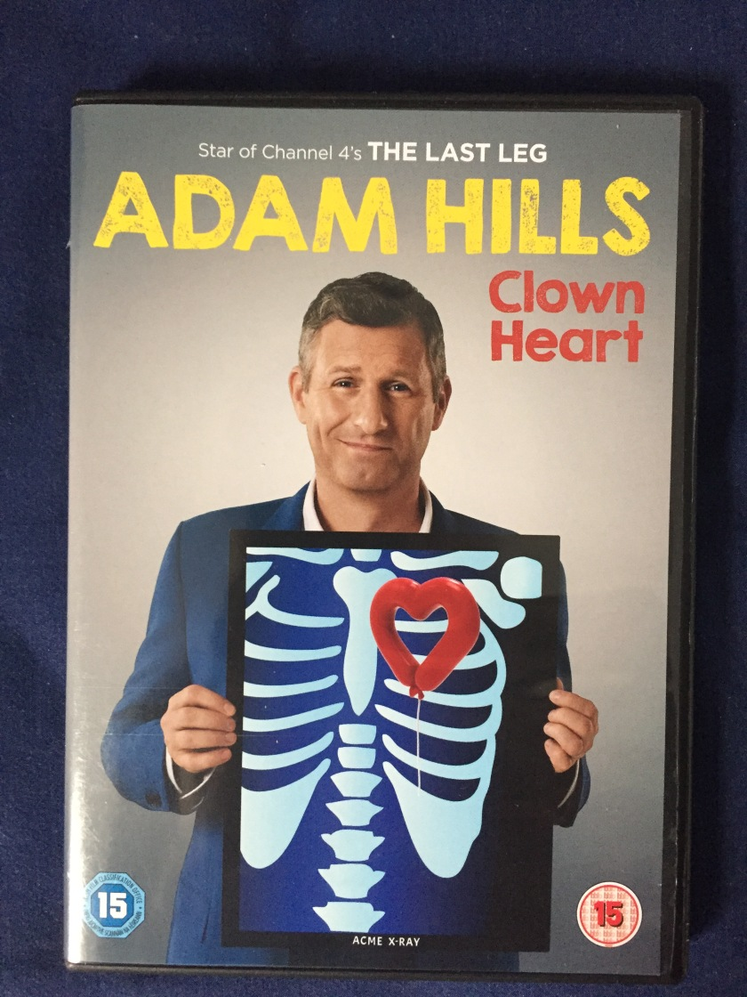 DVD case for Adam Hills - Clown Heart. Shows Adam smiling while holding up a mock X-ray in front of his chest. The X-ray shows a spine and ribcage, with a drawing of a long red balloon tied into a heart shape, floating in front of which his regular heart would be.