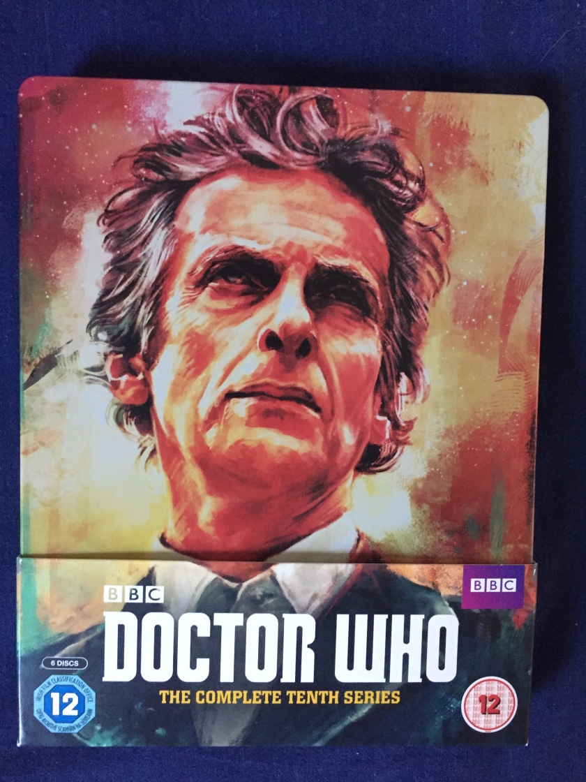 Blu-Ray case for Doctor Who - The Complete 10th series, showing a large portrait of Peter Capaldi's head and shoulders as the Doctor, in front of what appears to be a large explosion.