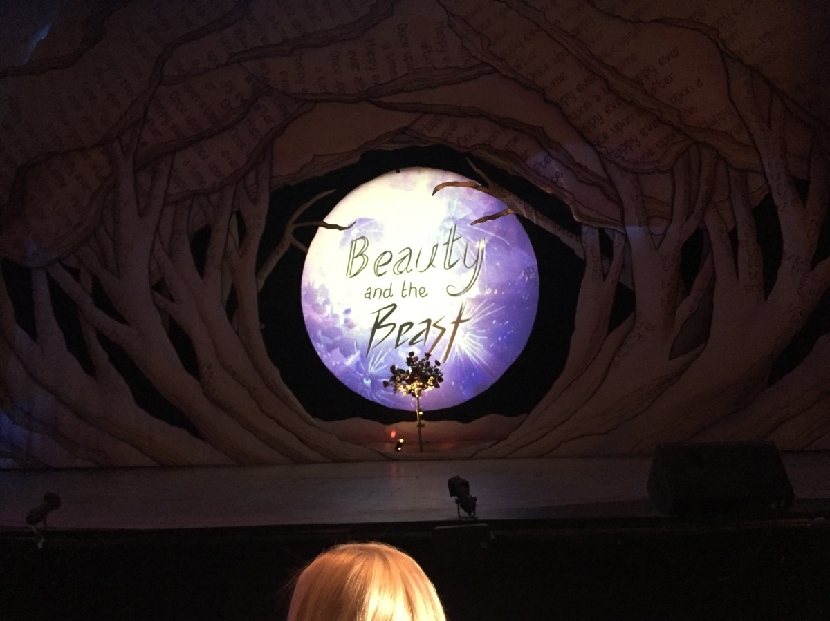 In a large clearing in a dark forest set on stage, a large bright moon-like circle apears in the centre, with the text Beauty & The Beast in black lettering on top. On stage in front of this stands a bunch of roses.