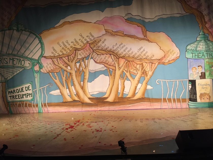 Stage backdrop artwork, a group of large cream coloured trees, with the text Once Upon A Time and Happy Ever After on some of their leafed tops. To their left are signs for the Parque De Treeumph and Paris Metro. And to their right is a sign saying Theatre.