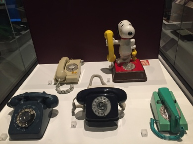A varied selection of 5 old style telephones with rotary dials. The most distinctive is one that has a model of Snoopy the dog standing up on the red base that has the dial, and holding the yellow receiver in his right hand.