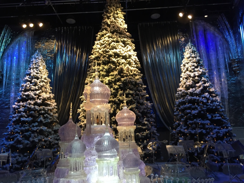 3 massive Christmas trees dusted with snow, in front of an ornate ice sculpture showing towers of various heights with bulbous domed tops.