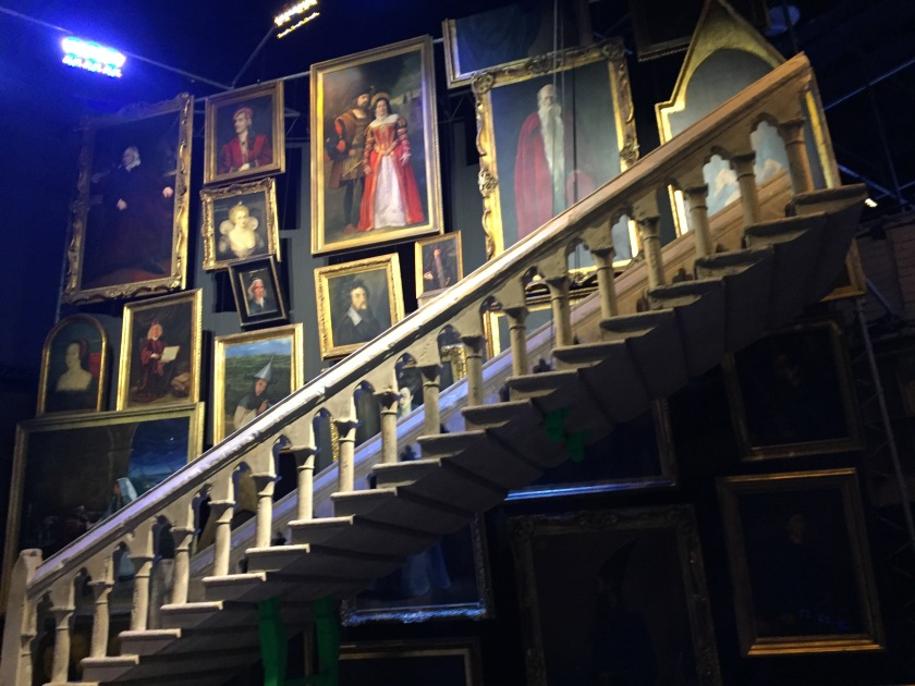 Staircase with portraits of various sizes on the wall behind it.