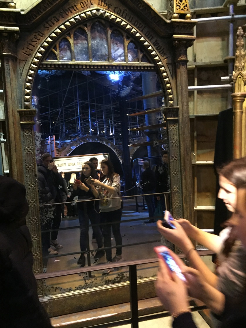 Two girls taking photos on their phones in front of the tall and ornate Mirror Of Erised.