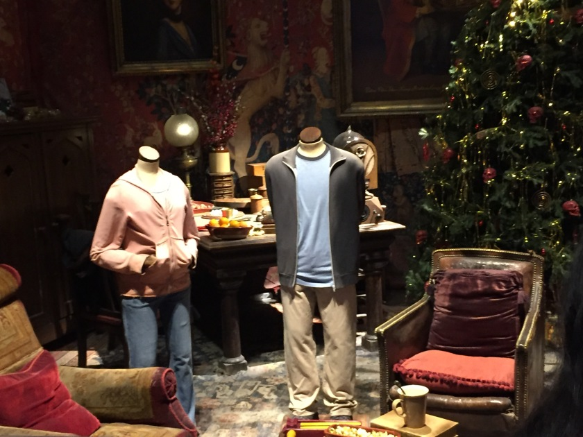 Headless mannequins dressed as Hermione and Harry, standing by chairs, a desk and a Christmas tree in the Gryffindor Common Room.