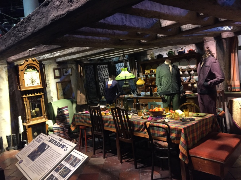 Inside The Burrow, home of the Weasleys, including wooden beams on the ceiling, a long dining table, headless mannequins wearing character's costumes, and a tall ornate clock with a pendulum.