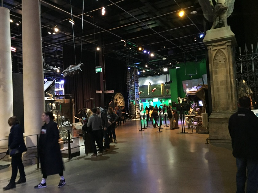 Inside the Harry Potter Studios, with a large walking area taking you past the various sets, props, costumes, etc, and a few people looking at the exhibits.