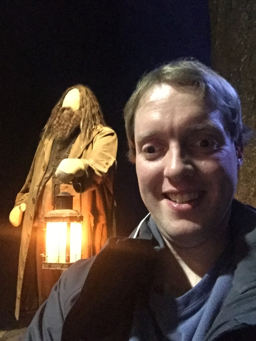 Selfie of Glen standing in front of a model of Hagrid holding a glowing lantern.