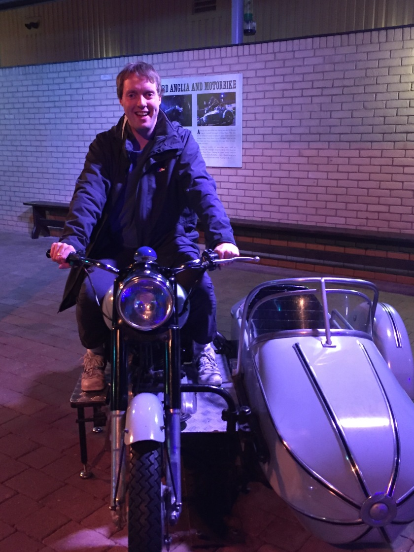 Glen smiling and sitting on Hagrid's motorbike, which has an empty white sidecar attached.