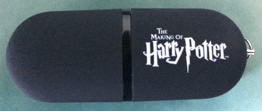 Black memory stick with the logo for The Making Of Harry Potter in white.lettering.