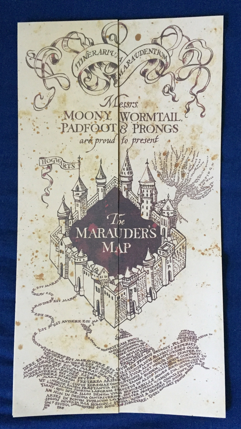 The folded-up Marauder's Map, tall and cream coloured, with decorative artwork in black ink. Near the top is the text Messrs Moony, Wormtail, Padfoot and Prongs are proud to present. Below this is a 4 walled square castle with the text The Marauder's Map in the centre on a black background.