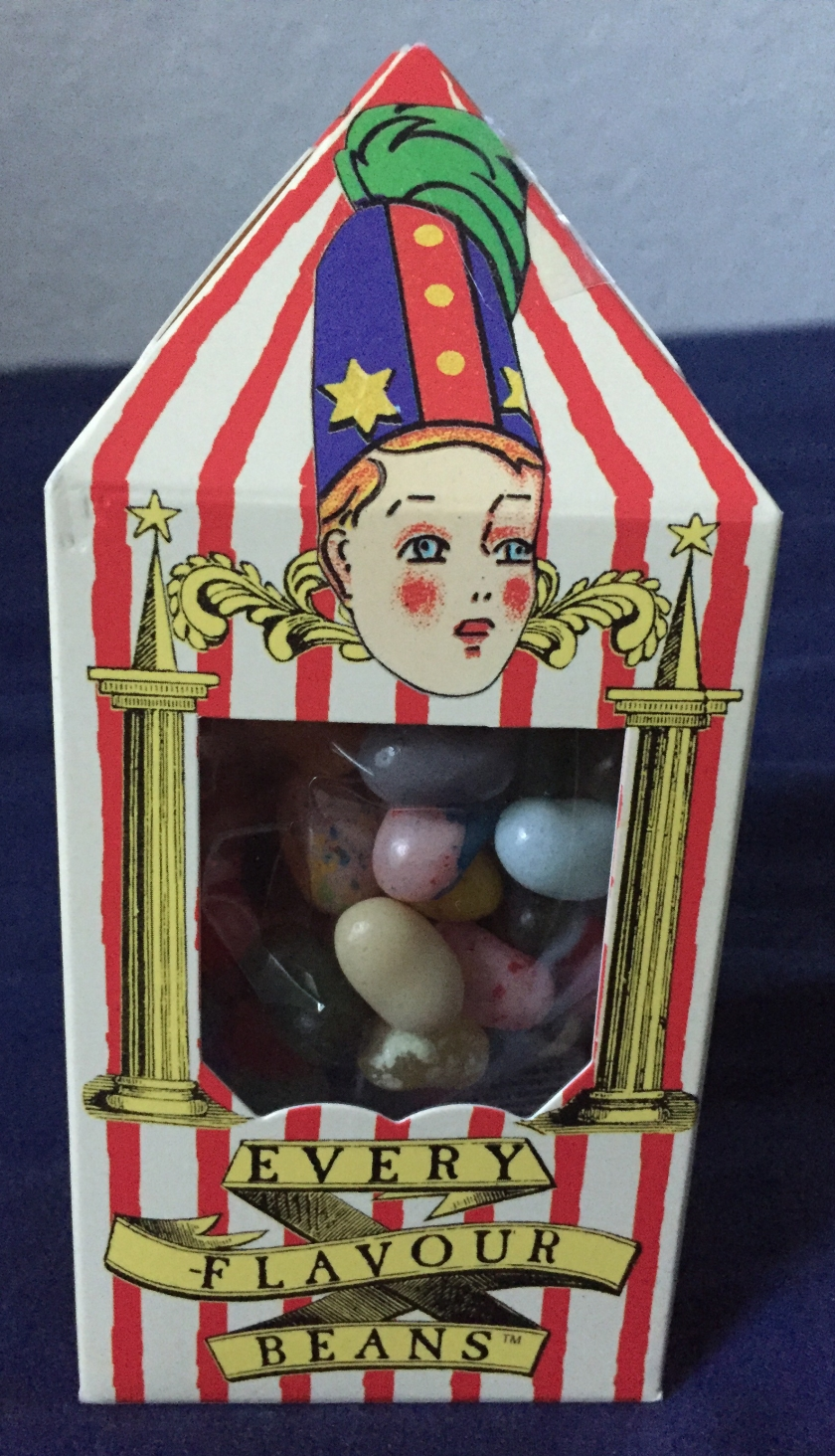 Red and white striped pack for Bertie Botts Every Flavour Beans, looking a bit like a tall, narrow circus tent. The rosy cheeked face of Bertie, wearing a tall blue and red hat, sits above the plastic window showing various different coloured beans.