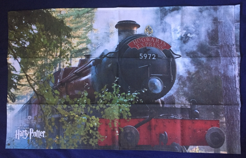 Tea towel showing a large image of the Hogwarts Express steam train passing by trees that line the edge of the railway.