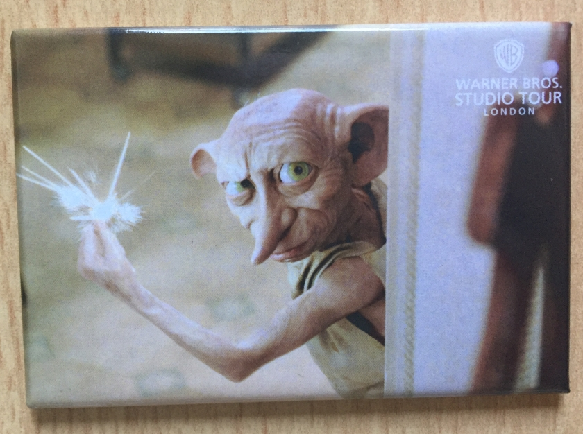 Fridge magnet showing Dobby the House Elf peering around a doorway and looking at us, producing sparks as he clicks his fingers.