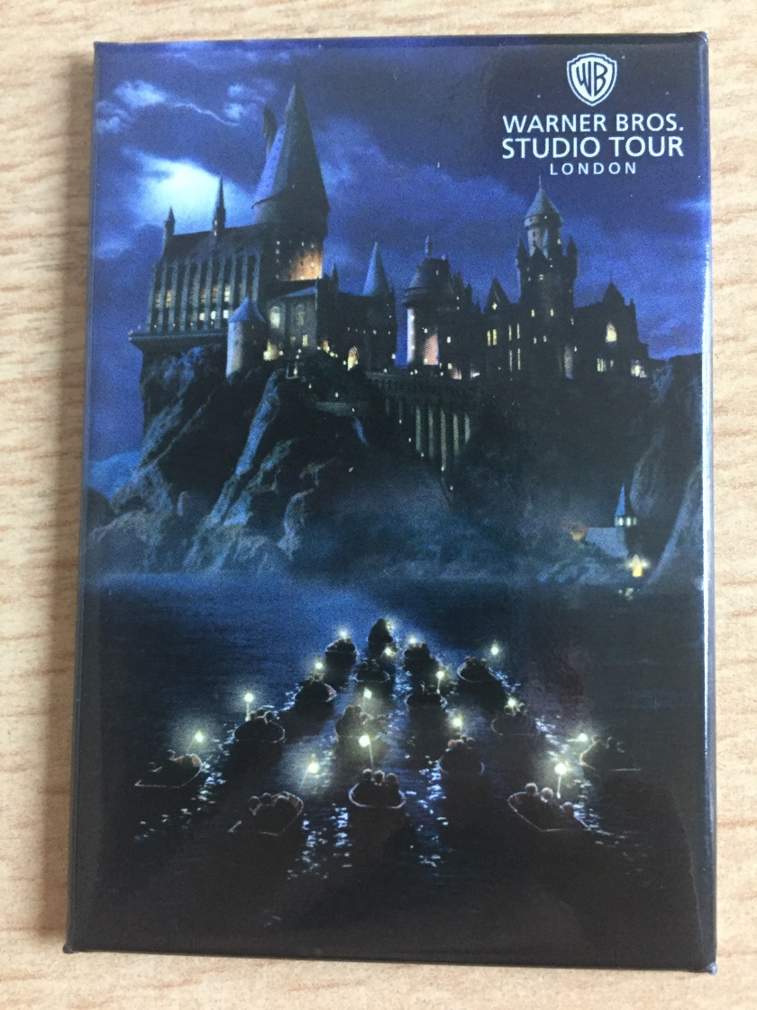 Photo magnet showing a night time scene, with people in small boats holding lights as they travel across the water, heading for the enormous Hogwarts Castle ahead of them.