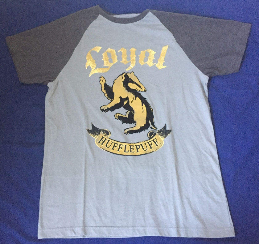 T-shirt with light grey body and dark grey short sleeves. The body has the word Loyal at the top in gold letters, below which is a large fold and black badger, and below that is a scroll across the chest with the word Hufflepuff.