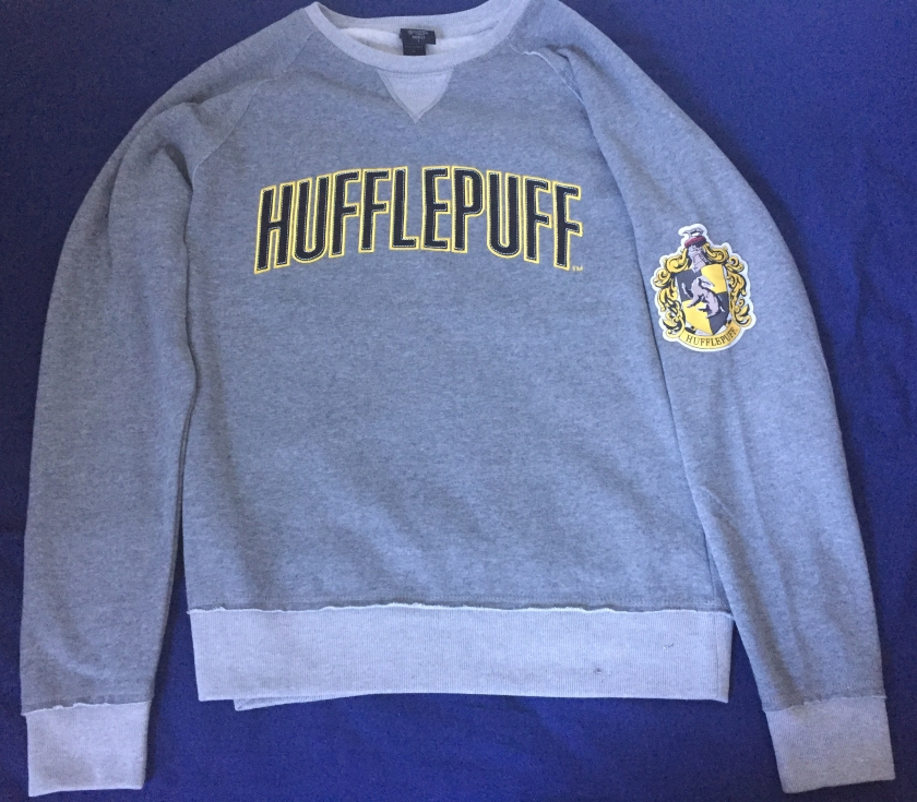 Grey sweater with the word Hufflepuff across the chest, in large black letters with gold edging. The official badge of Hufflepuff is on one sleeve, featuring a badger in the centre.
