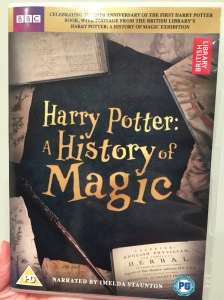 DVD cover for Harry Potter - A History Of Magic. The title is in gold lettering on a black background in the centre, surrounded by old papers and books and a magic wand.