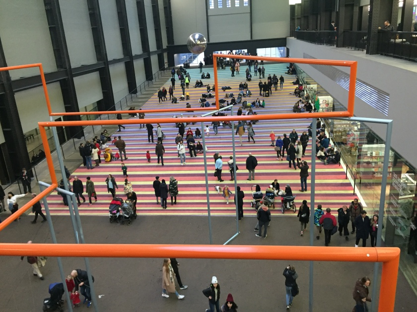 The long, wide entrance slope of the Turbine Hall at the Tate Modern, adorned with a multi-colour striped carpet on which people are sitting as others walk past. Above them, a large metal ball swings like a pendulum.