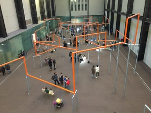 In the Turbine Hall of the Tate Modern, people are sitting on swings hanging down from orange bars, which criss-cross the space in a seemingly random pattern, with the seat of each swing holding 3 people.