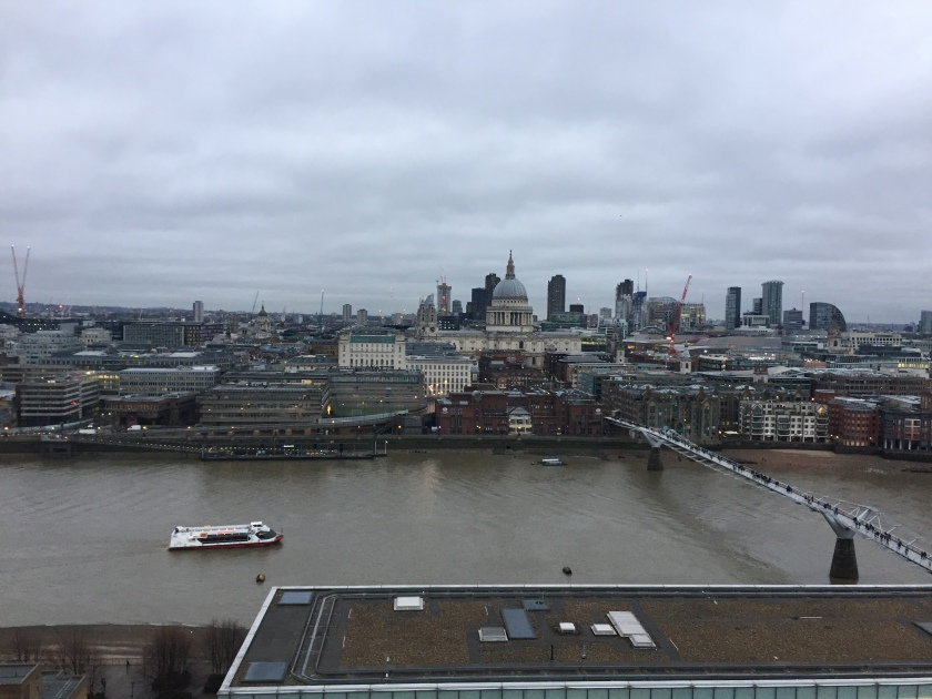 View across the Thames, high up on level 10 of the Tate Modern. St Paul's Cathedral is directly opposite, while on the river a tourist boat is travelling towards the Millennium Bridge on the right.