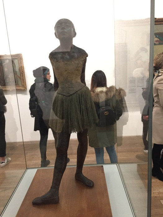 A dark coloured statue of a 14-year-old ballerina in a dancing top and skirt, posing as if in the middle of a dance, with one foot in front and one behind, toes pointing outwards.
