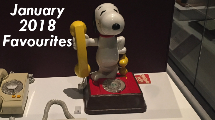 A phone consisting of a model of Snoopy, the white beagle cartoon dog, holding the yellow phone receiver in his right hand, and standing on a square red base which has the dial in front of his feet. White text overlaid on the left says January 2018 Favourites.