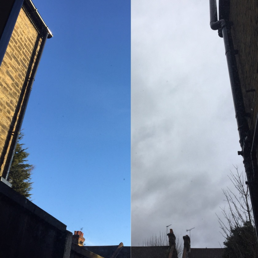 Combination of 2 photos side by side, showing the view up towards the sky from my back window downstairs, with the roofs of other houses just visible at the bottom. The left photo shows a clear blue sky, while the right shows a grey, cloudy sky. The photos are aligned to look like one shot of the view, with the sky changing halfway across.