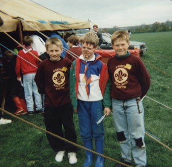 Me in the scouts as a kid, wearing blue trousers, a top that's half blue and half white, a green coat, and a blue and orange neckerchief. My face is painted with triangular marks all along my jaw (pointing up) and forehead (pointing down), and my nose is also painted. I'm standing in a field with 2 boys, who are wearing dark red sweaters with the Scout Association logo on.