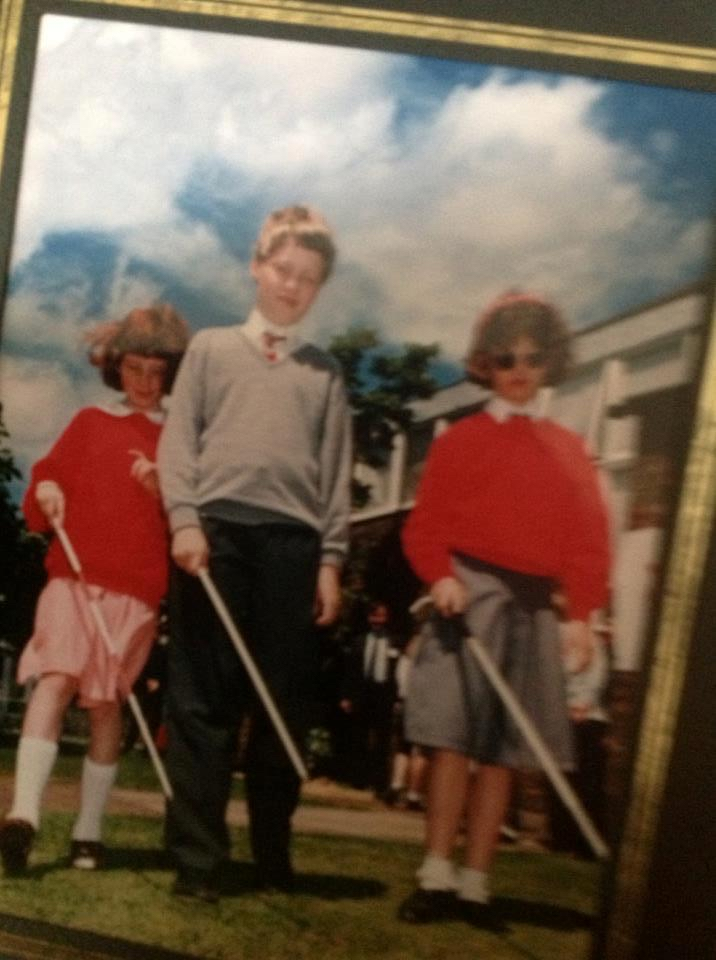A picture of me at school with 2 female friends, each of us holding a white symbol cane in front of us, diagonally across our legs. I'm in the middle, wearing a grey jumper and black trousers, whilst the girls are wearing red jumpers and either a pink or grey skirt respectively.