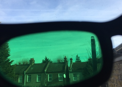 The blue sky and a row of houses below, as viewed through a green lens of my sunglasses. The glasses lens takes up most of the image, but above the glasses at the top is a small section of the blue sky as it normally looks, for comparison.