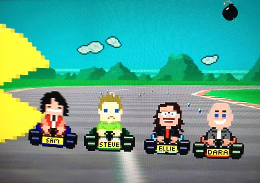 Image from the Go 8 Bit title sequence shows blocky computer graphic versions of Dara and his 3 main co-stars driving around a race track in small cars, while a large Pac-Man figure enters from the left.