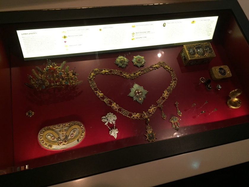 Glass case containing various jewellery items, including a large ornate necklace in the centre.