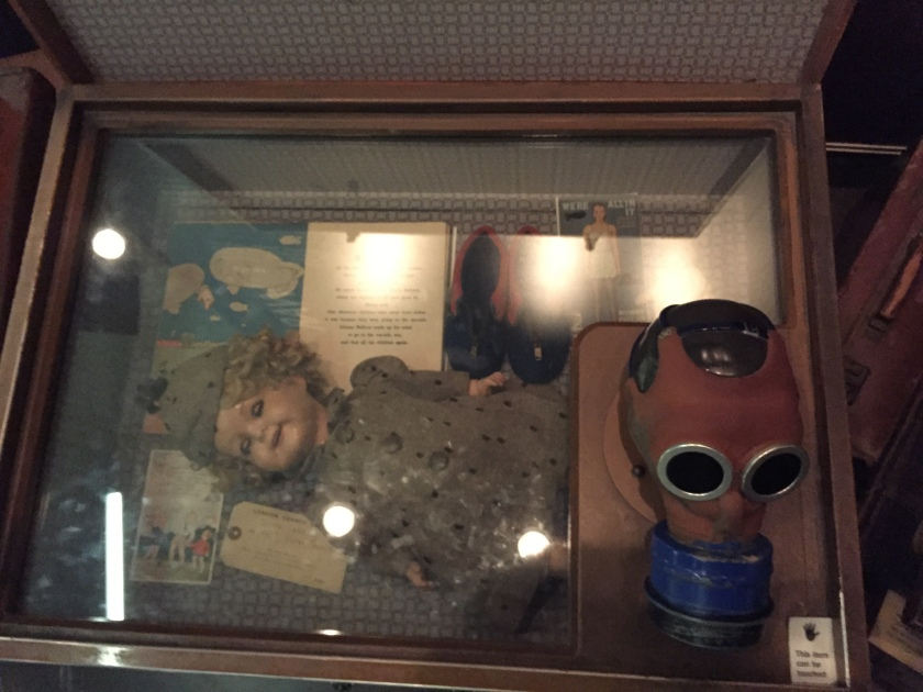 A case used for transporting a child's possessions during evacuation. This one contains a doll and books, and on to of the case is a child's gas mask, which you can touch.