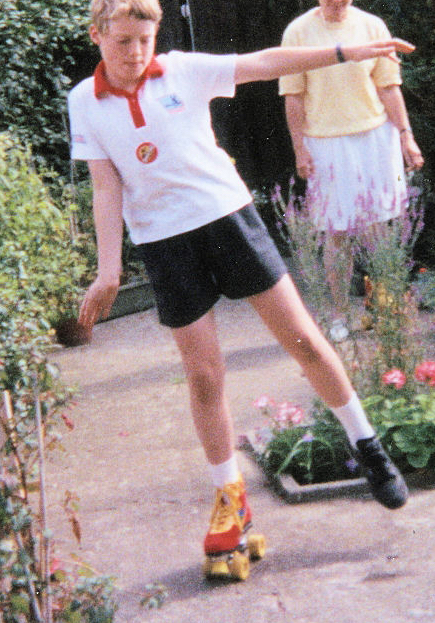 Me as a child in our back garden, wearing a white t-shirt and black shorts, reaching my arm out to the side as I balance on a red and yellow roller skate on my right foot. I'm wearing a regular black shoe on my left foot. My mother is watching in the background.